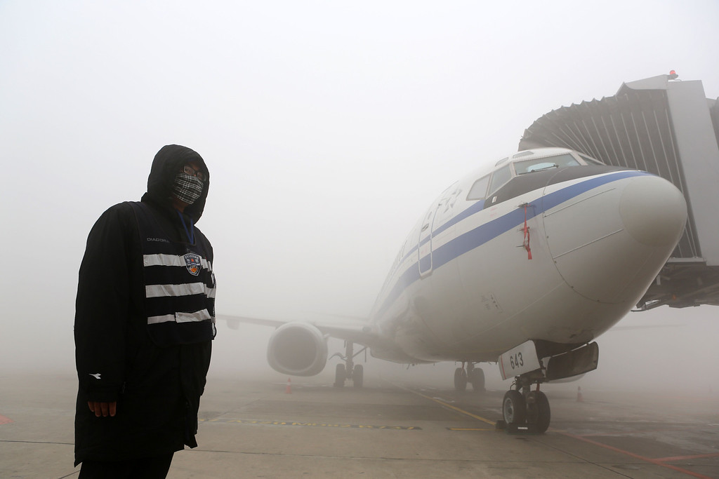 . A man stands next to an airplane under heavy smog in Harbin, northeast China\'s Heilongjiang province, on October 21, 2013.     AFP PHOTOSTR/AFP/Getty Images