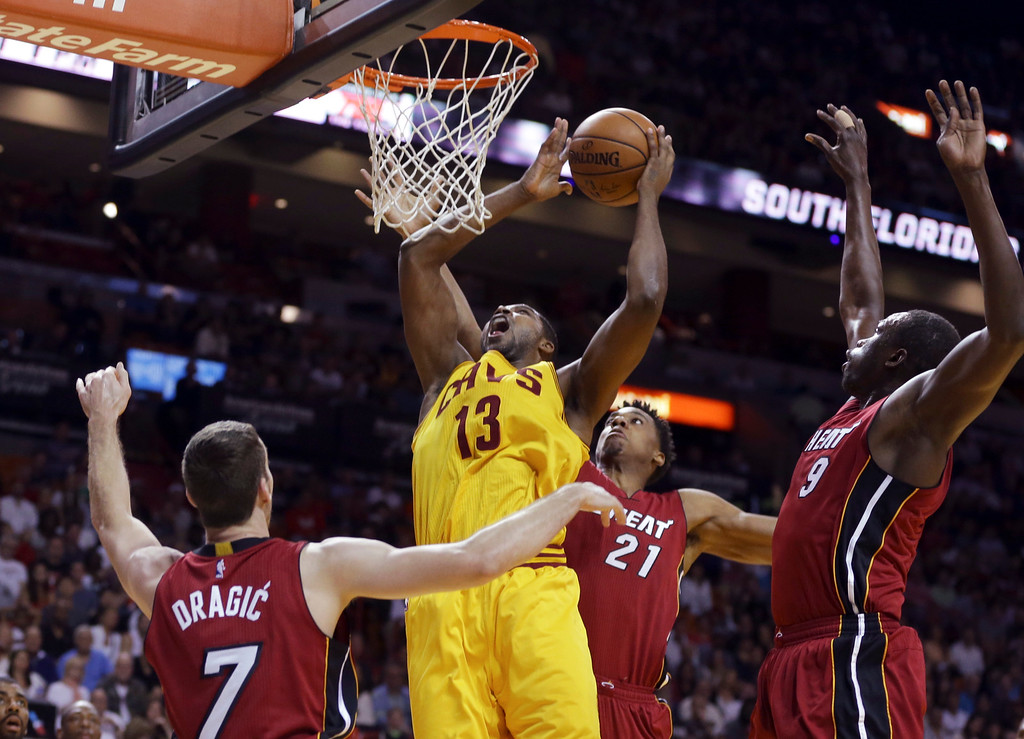 . Cleveland Cavaliers center Tristan Thompson (13) shoots as Miami Heat guard Goran Dragic (7), Hassan Whiteside (21), and Luol Deng (9) defend during the first half of an NBA basketball game, Saturday, March 19, 2016, in Miami. (AP Photo/Lynne Sladky)