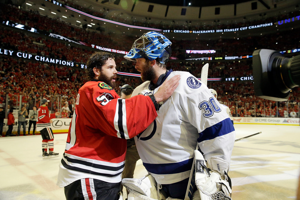 . Chicago Blackhawks goalie Corey Crawford (50) talks to Tampa Bay Lightning goalie Ben Bishop (30) after Game 6 of the NHL hockey Stanley Cup Final series on Monday, June 15, 2015, in Chicago. The Blackhawks defeated the Lightning 2-0 to win the series 4-2. (AP Photo/Nam Y. Huh)