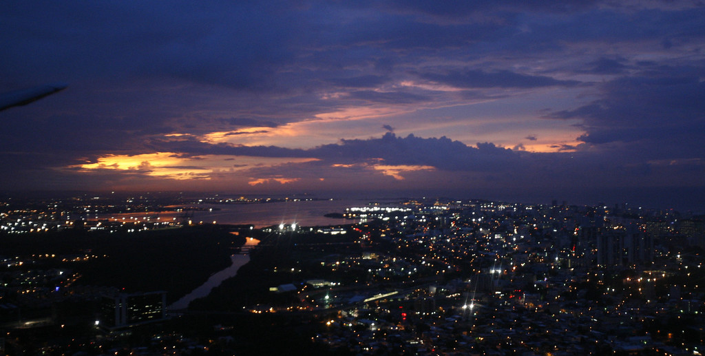 . The sun sets over San Juan, Puerto Rico as storm clouds from Tropical Storm Omar approach the area Tuesday, Oct. 14, 2008.  (AP Photo/Steve Helber)