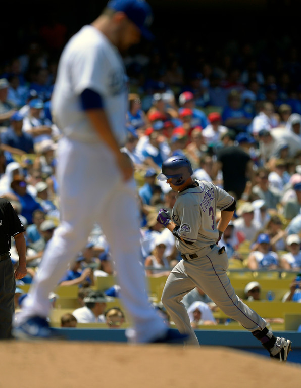 . Colorado Rockies\' Michael Cuddyer, right, rounds third after hitting a two-run home run as Los Angeles Dodgers starting pitcher Ricky Nolasco looks on during the fifth inning of their baseball game on Sunday, July 14, 2013, in Los Angeles. (AP Photo/Mark J. Terrill)