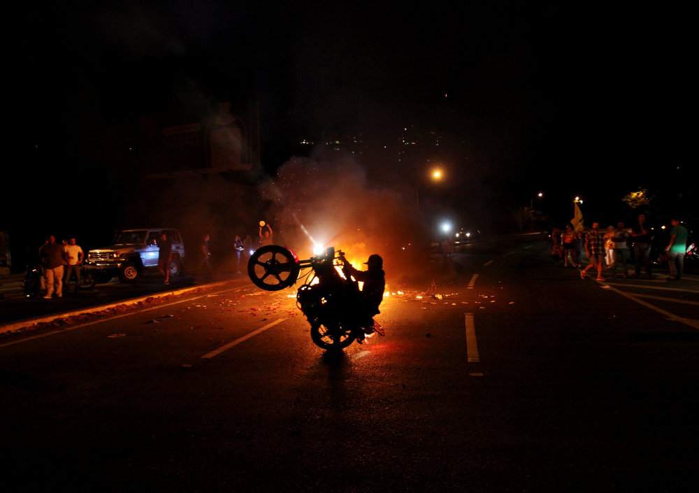 . An opposition supporter does a wheelie on his motorcycle as others bang pots during a protest against interim President Nicolas Maduro in Caracas, Venezuela, Monday, April 15, 2013. National Guard troops fired tear gas and plastic bullets to disperse students protesting the official results in Venezuela\'s disputed presidential election which gave Maduro a very narrow victory.   (AP Photo/Fernando Llano)