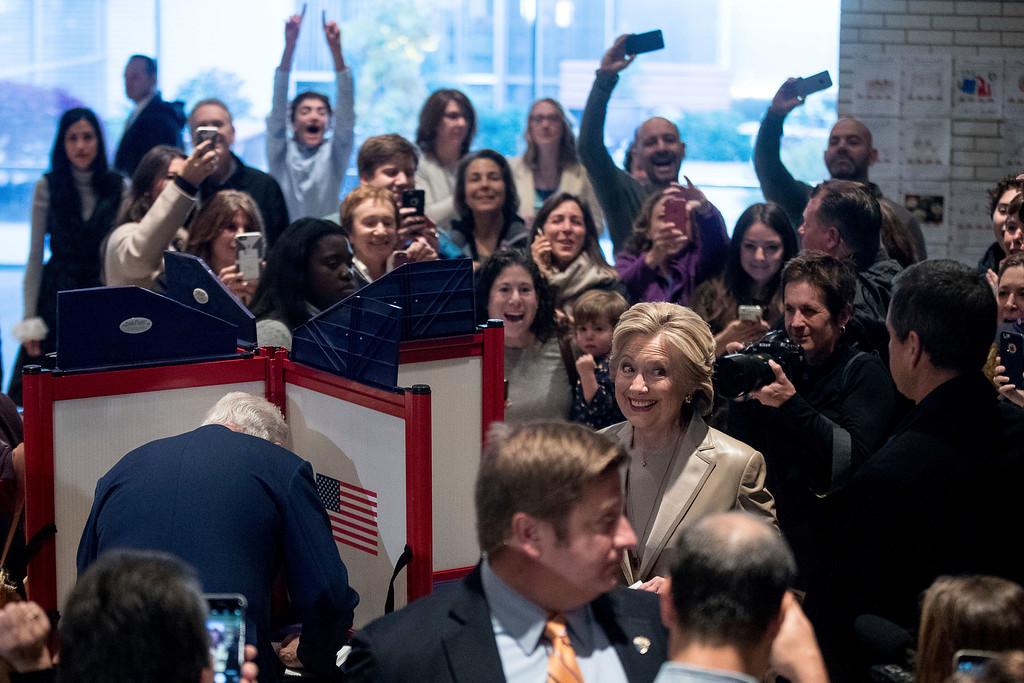 . Democratic presidential candidate Hillary Clinton, accompanied by her husband, former President Bill Clinton, left, smiles as she votes at Douglas G. Grafflin School in Chappaqua, N.Y., Tuesday, Nov. 8, 2016. At far left is senior aide Huma Abedin. (AP Photo/Andrew Harnik)