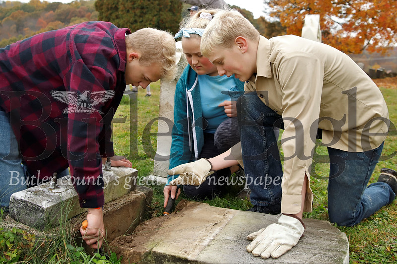 Jessie James Martineau (right)directs his brother Jason and sister Miranda to prepare to right a fallen tombstone in the Harmony Mennonite Meetinghouse  Cemetery. Martineau three other scouts from Boy Scout Troup 1606 worked on fixing up the cemetary for their Eagle Scout projects. Seb Foltz/Butler Eagle