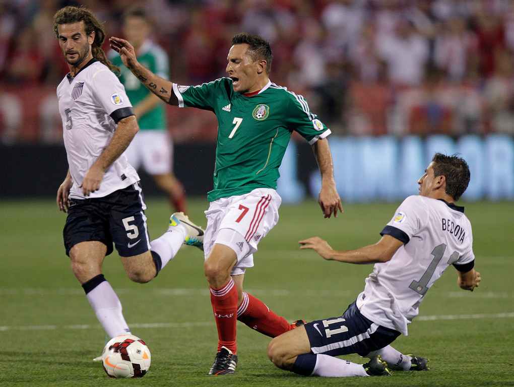 . Mexico\'s Christian Gimenez, center, is tripped by the United States\' Alejandro Bedoya, right, as Kyle Beckerman helps to defend during the first half of a World Cup qualifying soccer match Tuesday, Sept. 10, 2013, in Columbus, Ohio. (AP Photo/Jay LaPrete)