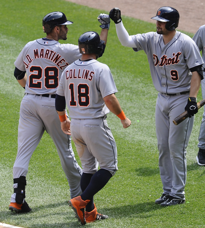 . Detroit Tigers  J.D. Martinez, left, gets high-fived by Detroit Tigers Nick Castellanos , right, as Detroit Tigers Tyler Collins looks on after Martinez hit a two run home run during the sixth inning of baseball game against the Chicago White Sox in Chicago on Sunday, June 7,  2015. Collins also scored on the hit. (AP Photo/Matt Marton)