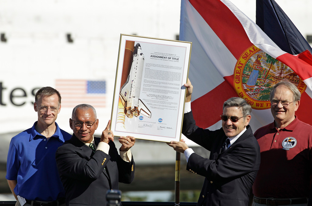 . Astronaut Chris Ferguson, far left, commander of the final space shuttle Atlantis mission stands with, starting second from left, NASA Administrator Charles Bolden, Kennedy Space Center director Bob Cabana and former astronaut Karol Bobko, the commander of the first Atlantis mission, hold up an Assignment of Title document  during a ceremony to retire Atlantis at the Kennedy Space Center,  Friday, Nov. 2, 2012, in Cape Canaveral, Fla. (AP Photo/John Raoux)