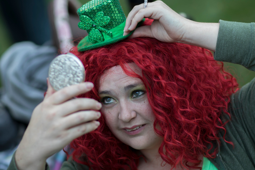 . Aimee Norton puts the finishing touch on her outfit before the start of the St. Patrick\'s Day parade, Tuesday, March 17, 2015, in Savannah, Ga. Organizers have long billed the Savannah St. Patrick\'s Day parade as the nationís second largest based on the size of the procession, rather than the number of people watching. (AP Photo/Stephen B. Morton)