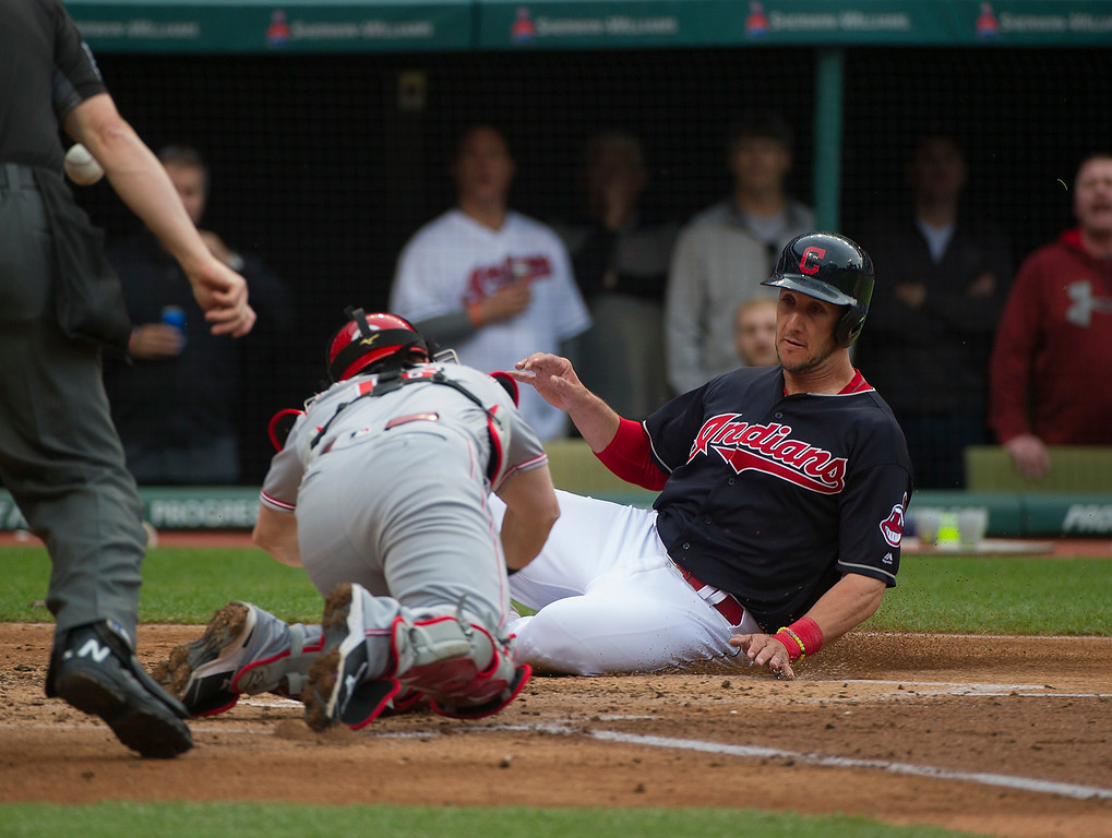 . Cleveland Indians Yan Gomes slides safely into home plate as Cincinnati Reds catcher Tucker Barnhart lunges to make the tag, during the second inning of a baseball game in Cleveland, Tuesday, May 17, 2016. (AP Photo/Phil Long)