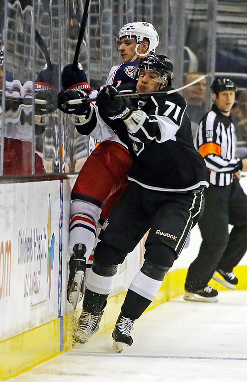 . Los Angeles Kings center Jeff Carter (77) and Columbus Blue Jackets left wing Matt Calvert (11) slam into the boards in the first period of an NHL hockey game in Los Angeles Thursday, April 18, 2013. (AP Photo/Reed Saxon)
