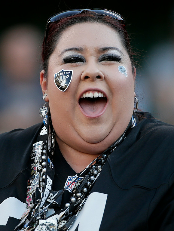 . An Oakland Raiders fan cheers during an NFL preseason football game between the Raiders and the Detroit Lions in Oakland, Calif., Friday, Aug. 15, 2014. (AP Photo/Marcio Jose Sanchez)