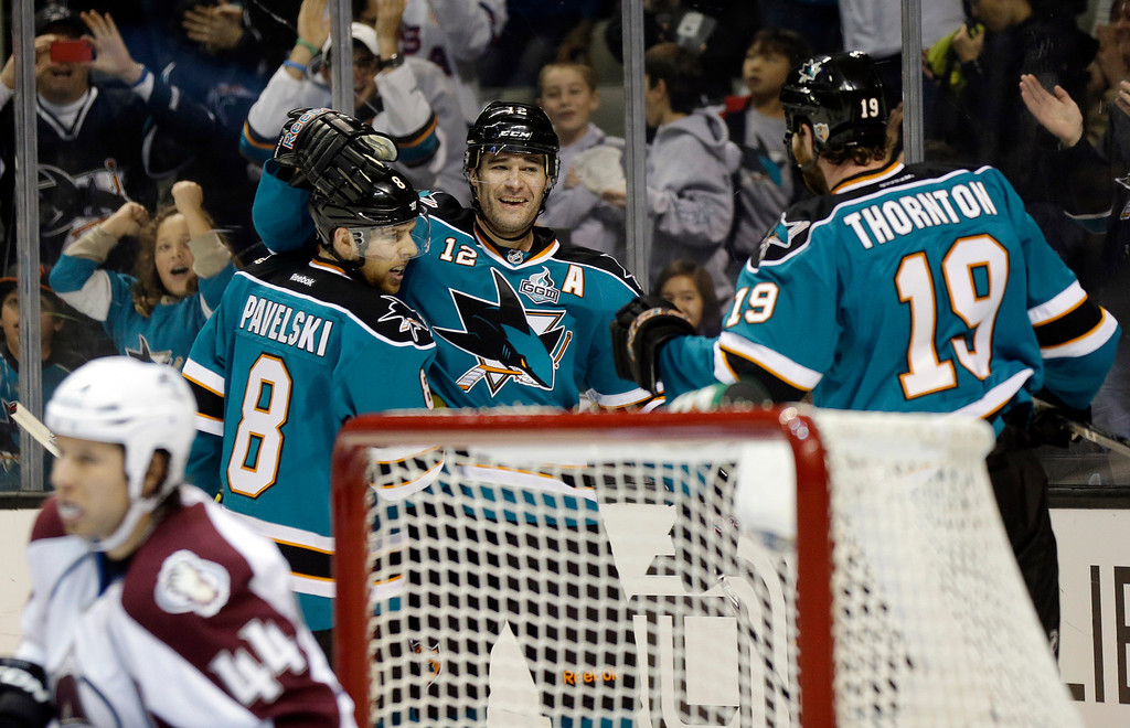 . San Jose Sharks center Patrick Marleau (12) celebrates with teammates Joe Pavelski (8) and Joe Thornton (19) after scoring past Colorado Avalanche defenseman Ryan Wilson (44) during the first period of an NHL hockey game in San Jose, Calif., Saturday, Jan. 26, 2013. (AP Photo/Marcio Jose Sanchez)