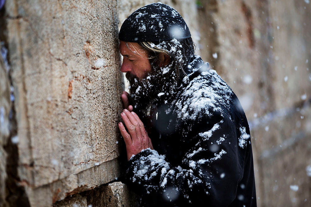 Description of . Snow falls as an ultra-orthodox Jewish man prays at the Western Wall in Jerusalem's Old City, Thursday, Jan. 10, 2013. Stormy weather conditions continued on Thursday with snow, torrential rains and strong winds across the region. (AP Photo/Bernat Armangue)