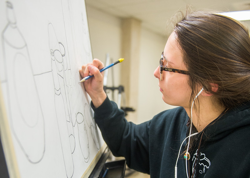Student Paige Lilley adds some final touches to her still life midterm project in the Center for Arts.