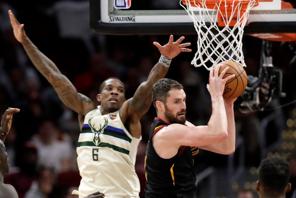 . Cleveland Cavaliers\' Kevin Love, right, looks to pass against Milwaukee Bucks\' Eric Bledsoe (6) in the second half of an NBA basketball game, Monday, March 19, 2018, in Cleveland. (AP Photo/Tony Dejak)