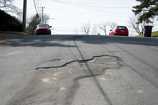 03/28/19 Wesley Bunnell | Staff Large potholes line Sunrise St in New Britain on Thursday afternoon. A resident reported the potholes using the See Click Fix app earlier today.