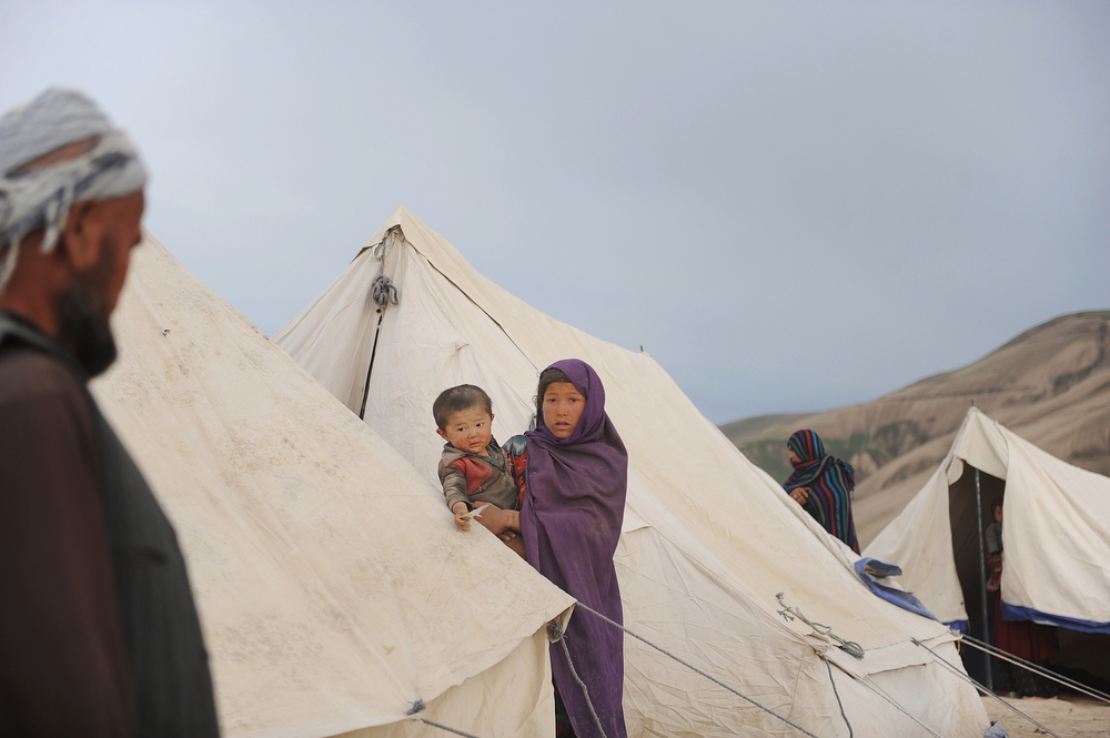 . Afghan people stand near their tents at the site of a landslide at the Argo district in Badakhshan on May 3, 2014. Landslides buried a village in northern Afghanistan on Friday, killing at least 350 people and leaving thousands of others feared dead, as rescuers searched desperately for survivors trapped under the mud. Villagers at the disaster site in Badakhshan province used shovels to dig through rocks and dirt, with national authorities, the United Nations and the US-led military force all racing to assess the damage and provide help. (FARSHAD USYAN/AFP/Getty Images)