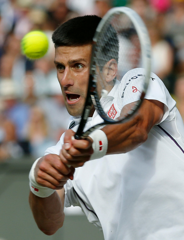 . Serbia\'s Novak Djokovic plays a return to Switzerland\'s Roger Federer during their men\'s singles final match at the All England Lawn Tennis Championships in Wimbledon, London, Sunday, July 6, 2014. (AP Photo/Sang Tan, Pool)