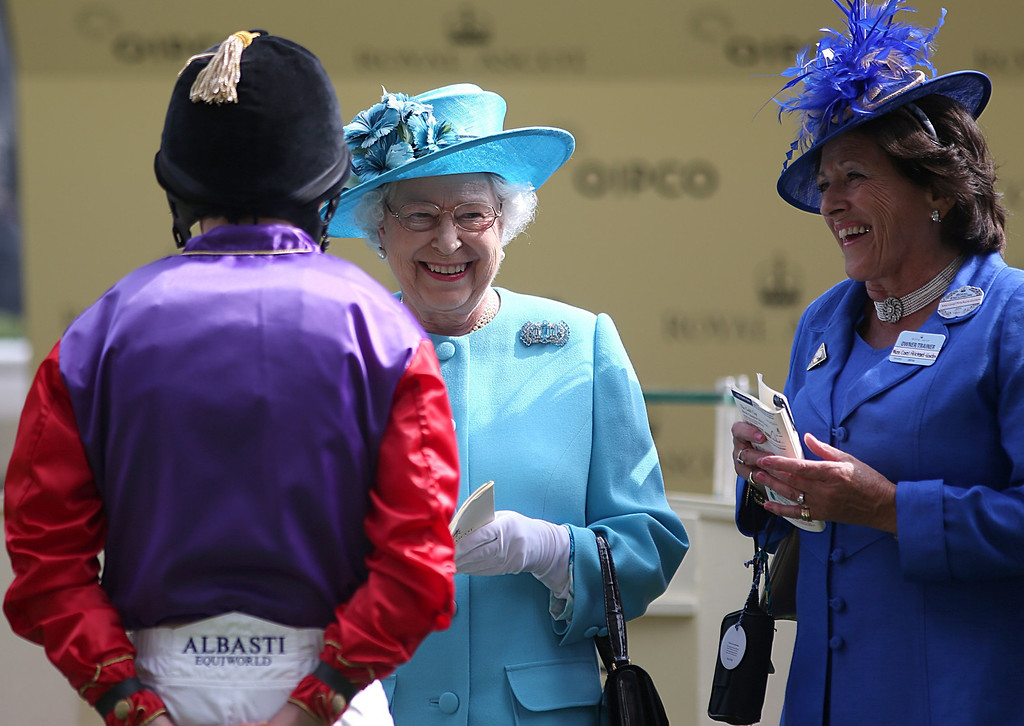 . Britain\'s Queen Elizabeth II, centre,  speaks with jockey Ryan Moore, back to camera, who rode her horse Estimate into second place in the Gold Cup at the Royal Ascot horse racing meeting in Ascot England Thursday June 19, 2014. (AP Photo/Steve Parsons/PA)