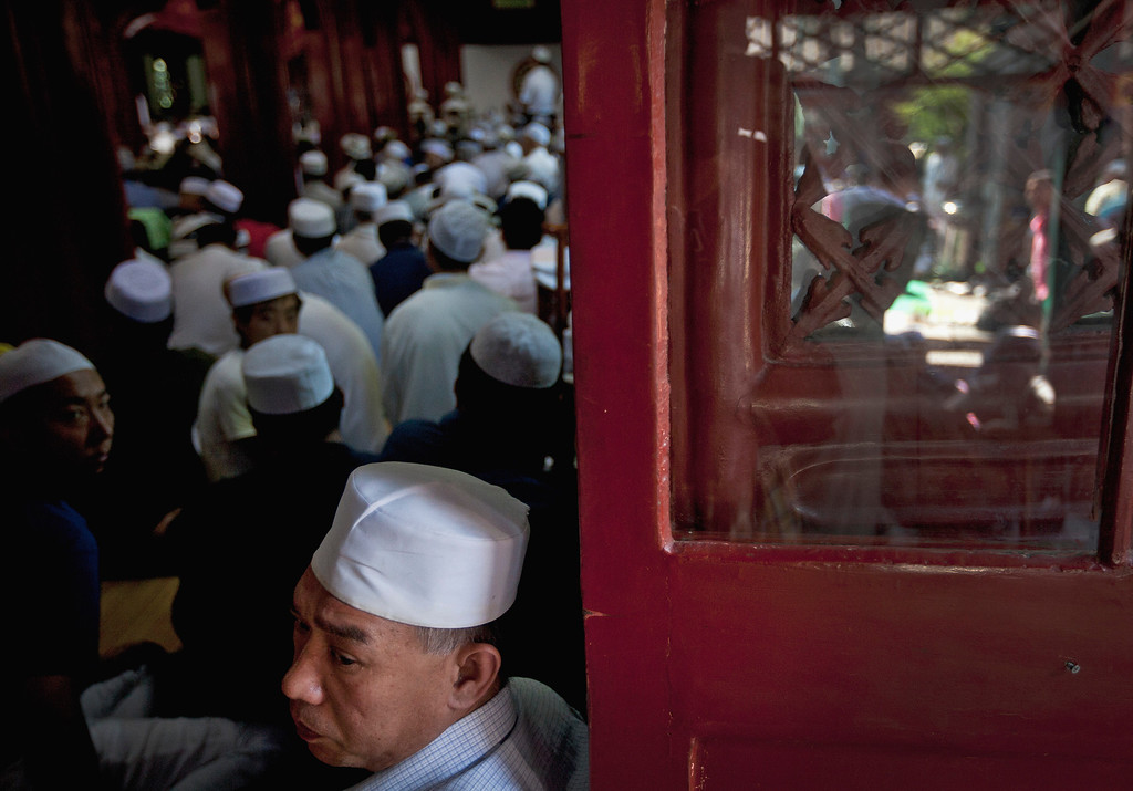 . A Muslim man looks out from a worship hall as he attends an Eid al-Fitr morning prayer session with others at the Niujie Mosque in Beijing, China Thursday, Aug. 8, 2013. Muslims in China celebrate the Eid al-Fitr that marks the end of the holy fasting month of Ramadan. (AP Photo/Andy Wong)