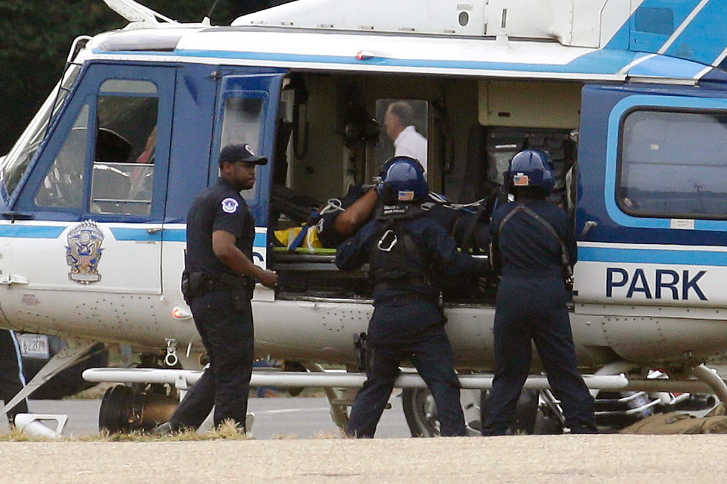 . A U.S. Park Police helicopter is loaded on the Mall in Washington, Thursday, Oct. 3, 2013, with a victim from a shooting. Police say the U.S. Capitol has been put on a security lockdown amid reports of possible shots fired outside the building.  (AP Photo/Alex Brandon)