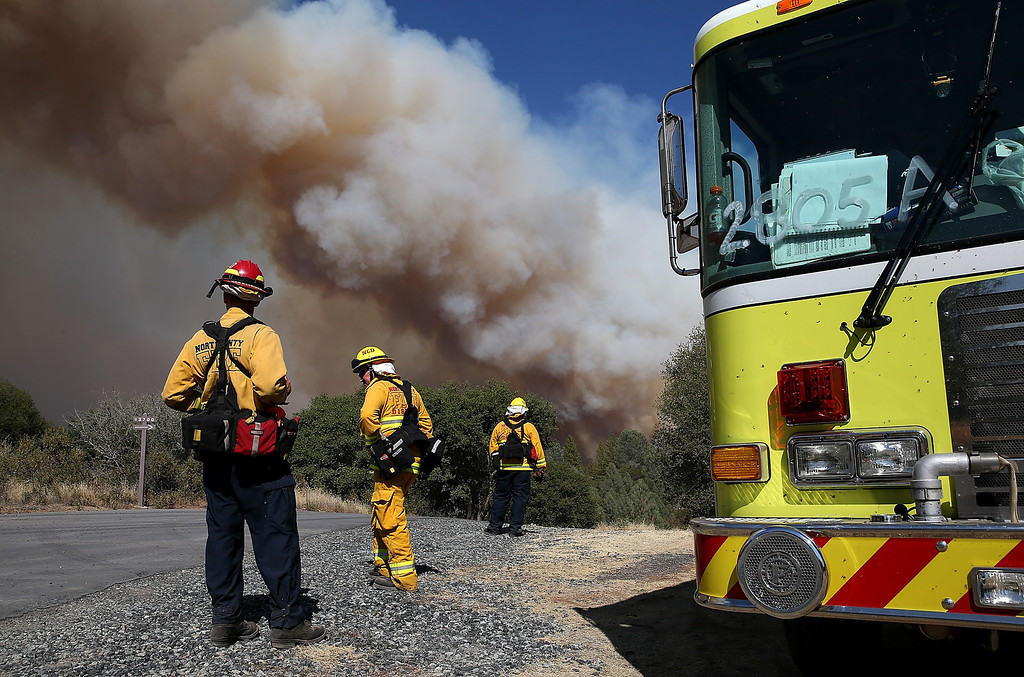 . GROVELAND, CA - AUGUST 22:  Firefighters monitor a plume of smoke from the Rim Fire on August 22, 2013 in Groveland, California. The Rim Fire continues to burn out of control and threatens 2,500 homes outside of Yosemite National Park. Over 1,000 firefighters are battling the blaze that was reduced to only 2 percent containment after it nearly tripled in size overnight.  (Photo by Justin Sullivan/Getty Images)