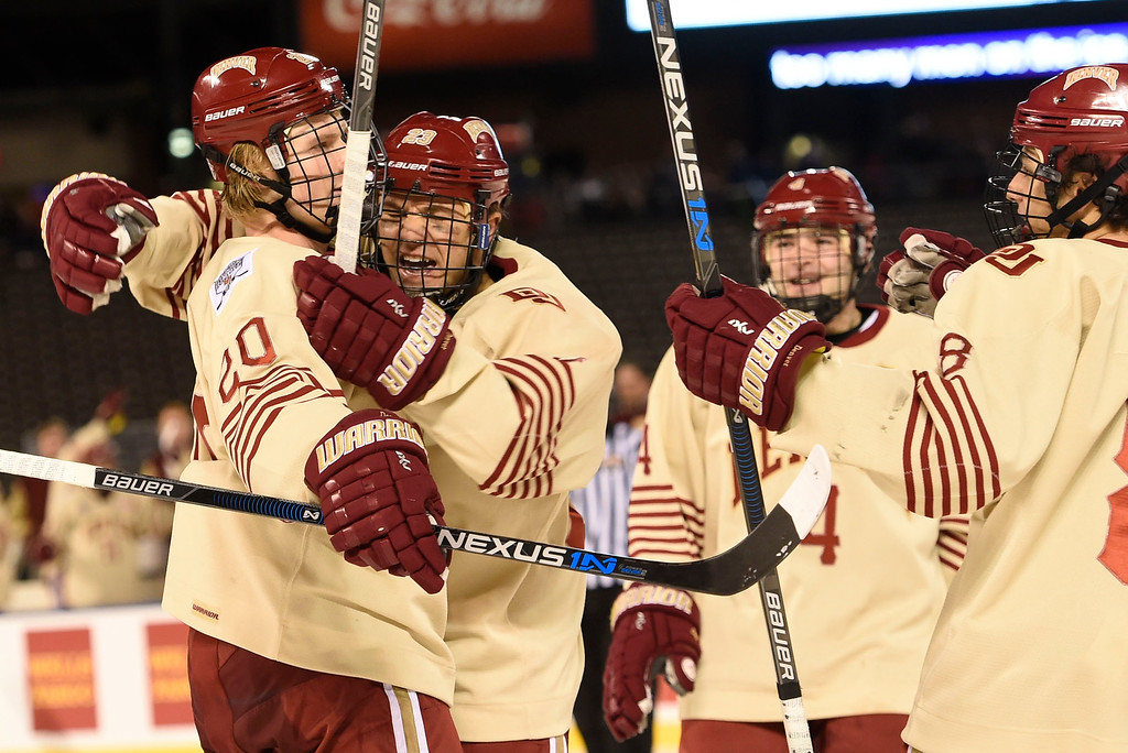 . Denver Pioneers forward Matt Marcinew (23) celebrates a goal by Denver Pioneers forward Danton Heinen (20) in the third period against Colorado College Tigers during the Battle On Blake February 20, 2016 at Coors Field. Denver Pioneers defeated Colorado College Tigers 4-1 in front of 35,144 hockey fans.  (Photo By John Leyba/The Denver Post)