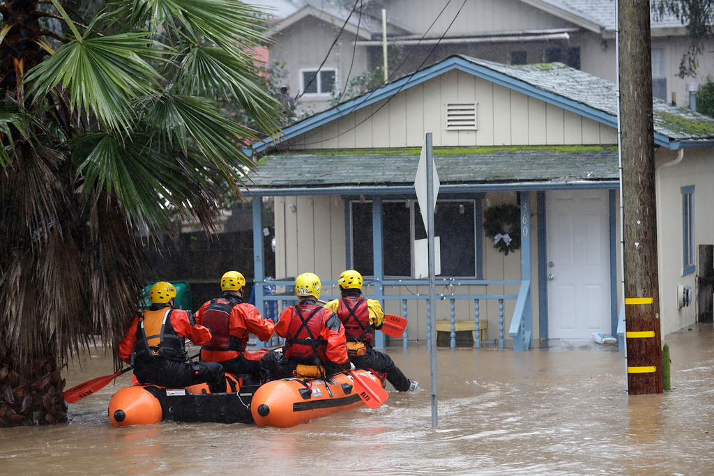 . Rescue crews survey a flooded neighborhood Tuesday, Feb. 7, 2017, in Felton, Calif. Flash flood watches are in place for parts of Northern California down through the Central Coast as heavy rains swamp roads and threaten to overtop rivers and creeks. (AP Photo/Marcio Jose Sanchez)