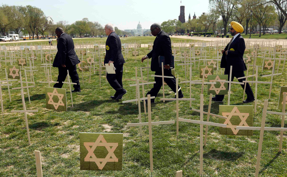 "Description of . With the U.S. Capitol in the background, members of the clergy pass through a field of crosses symbolizing grave markers on the National Mall in Washington April 11, 2013. The PICO National Network\'s Lifelines to Healing and Sojourners are holding a 24-hour vigil featuring a gathering of Newtown clergy and 3,300 grave markers to ""remind Congress action is needed on gun violence prevention\"". The number 3,300 represents the supposed number of people who have died as a result of gun violence since the tragedy in Newtown.  REUTERS/Kevin Lamarque"
