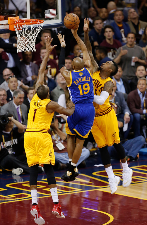 . Golden State Warriors guard Leandro Barbosa (19) attempts a shoot between Cleveland Cavaliers forward James Jones (1) and guard J.R. Smith (5) during the second half of Game 3 of basketball\'s NBA Finals in Cleveland, Tuesday, June 9, 2015. (AP Photo/Paul Sancya)