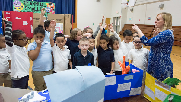 03/27/18 Wesley Bunnell | Staff First grade teacher Mrs. Poff selects students who raised their hands to answer questions at the Smalley Academy 2nd Annual Smalley Science Fair on Tuesday morning. Students include Davian Blake, far L, Marleigh Marshall, Austin Greener, middle looking at project.