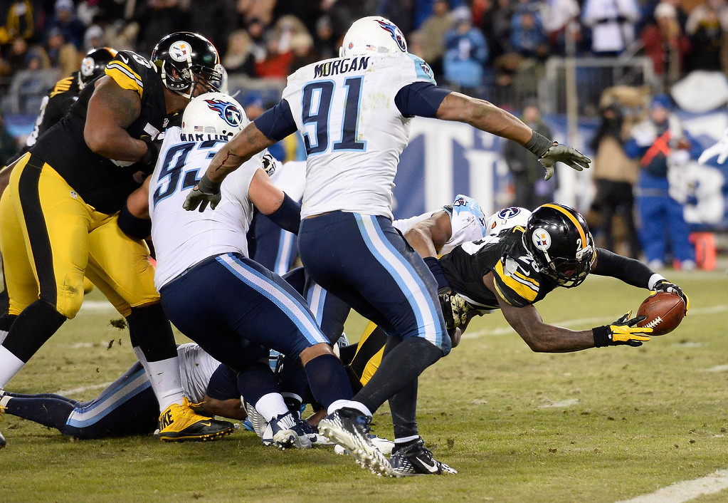 . Pittsburgh Steelers running back Le\'Veon Bell (26) scores a touchdown on a 5-yard run against Tennessee Titans defenders Mike Martin (93) and Derrick Morgan (91) in the second half of an NFL football game Monday, Nov. 17, 2014, in Nashville, Tenn. (AP Photo/Mark Zaleski)
