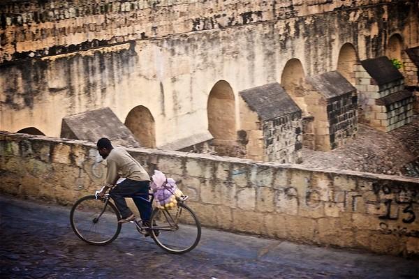 A man rides a bicycle along a cobblestone road past an old aqueduct in Oaxaca de Juarez, Oaxaca, Mexico.