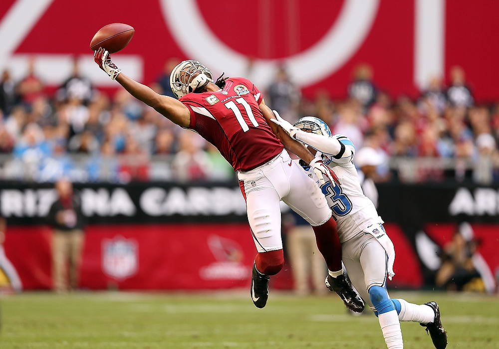 . Wide receiver Larry Fitzgerald #11 of the Arizona Cardinals is unable to make a leaping reception under pressure from cornerback Chris Houston #23 of the Detroit Lions during the NFL game at the University of Phoenix Stadium on December 16, 2012 in Glendale, Arizona.  The Cardinals defeated the Lions 38-10. (Photo by Christian Petersen/Getty Images)