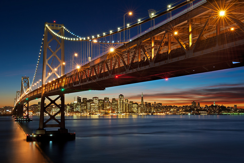 "Willie and I have been wanting to take the now popular San Francisco skyline photo from under the Bay Bridge for a while now. The photo is much much nicer during the holiday time when the lights outlining the buildings are turned on and a bright white light (called The Beacon) is turned on at the Transamerica Building (the triangular building). Willie checked the webcams for a couple nights this week and it looked like The Beacon was on, and I got confirmation from a friend in the city that it was also on (although, she described it as a ""blinking light"" -- I should have known this was bad information … read more about that).  We left work early and headed out to Treasure Island with plenty of time to find parking, hike up the hill, find ""the spot"" and then get setup. Unfortunately when US-101 and I-280 merged we hit a HUGE Friday afternoon holiday traffic. We arrived at Treasure Island much much later than planned (almost an hour later), and had to high tail it up the hill and over the Bay Bridge (we were both sweating pretty badly). After hopping the guard rail we actually found the spot pretty easily (just as we were walking over the Bridge a CalTrans truck drove by and screamed over the loud speaker ""No photographs from this side of the bridge."" We kept walking). We scouted out the area for a while, found our spots and then waited for the light to get nice.  Luckily for us there was an absolutely BEAUTIFUL sunset that night, which makes the photo much more interesting. As the sun went down we could start making out the lights on the buildings, first some random window lights, then the building outlines, and then a light on top of the Transamerica Building. A light … a red blinking light … NOT the white BEACON we were hoping for. In fact, The Beacon *never* showed up for us :( We still came away with a great shot but both Willie and I felt jipped because The Beacon is the icing on the cake of this classic shot. We're going to have to re-attempt it another time :(  Nikon D700 w/Nikkor 24-70mm f/2.8G ED AF-S: 42mm, f/16, 30 sec, ISO 125 No filters, NOT an HDR (all from 1 exposure)"