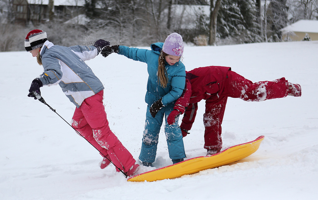. From left,  Maeve Talty, 10, Caroline Talty, 8, and Maureen Greenwell, 8, all from Mt. Lookout, Ohio, try to stay on a sled together at the Cincinnati Observatory Center in Hyde Park on Wednesday, March 6, 2013.    Hundreds of schools including in some of Ohio\'s biggest public districts called off classes Wednesday. (AP Photo/The Cincinnati Enquirer, Leigh Taylor)