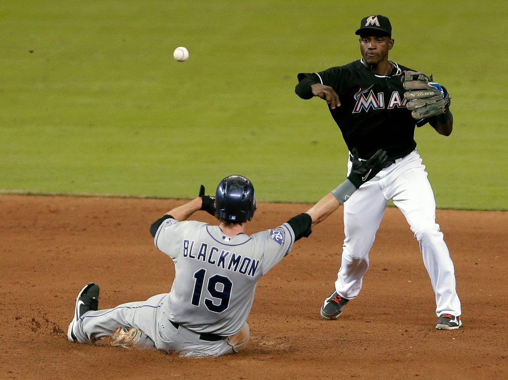 . Miami Marlins shortstop Adeiny Hechavarria throws to first to complete the double play as Colorado Rockies\' Charlie Blackmon slides into second during the fifth inning of a baseball game, Friday, Aug. 23, 2013 in Miami. Dexter Fowler was out at first. (AP Photo/Wilfredo Lee)