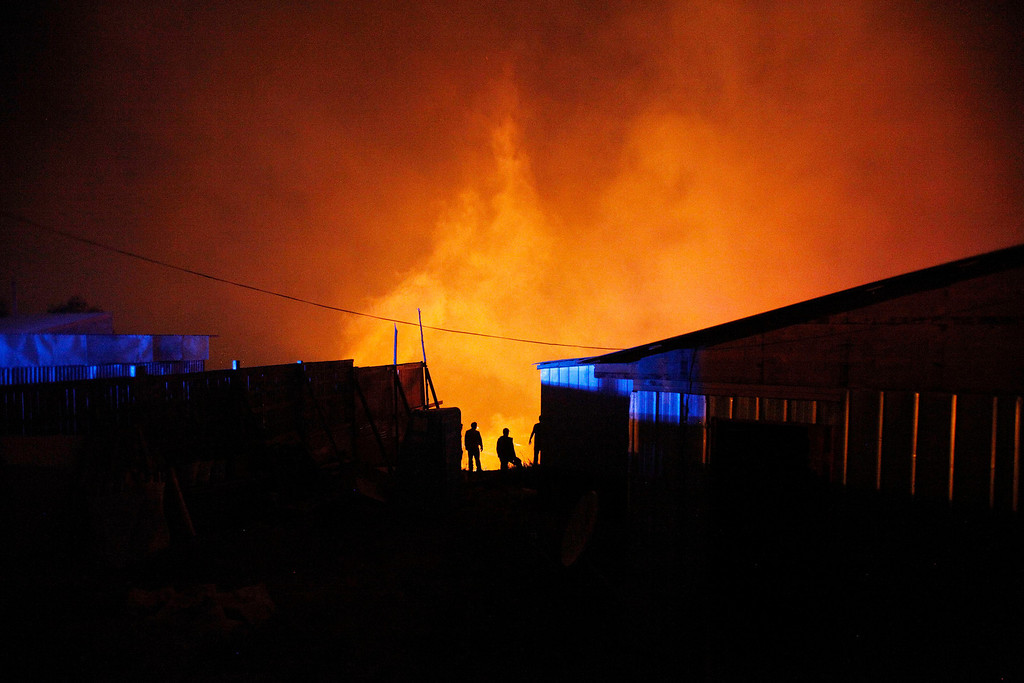 . A group of firefighters stand next to burning homes as a forest fire rages towards urban areas in the city of Valparaiso, Chile, Sunday April 13, 2014. . Authorities say the fires have destroyed hundreds of homes, forced the evacuation of thousands and claimed the lives of at least seven people.  ( AP Photo/ Luis Hidalgo)