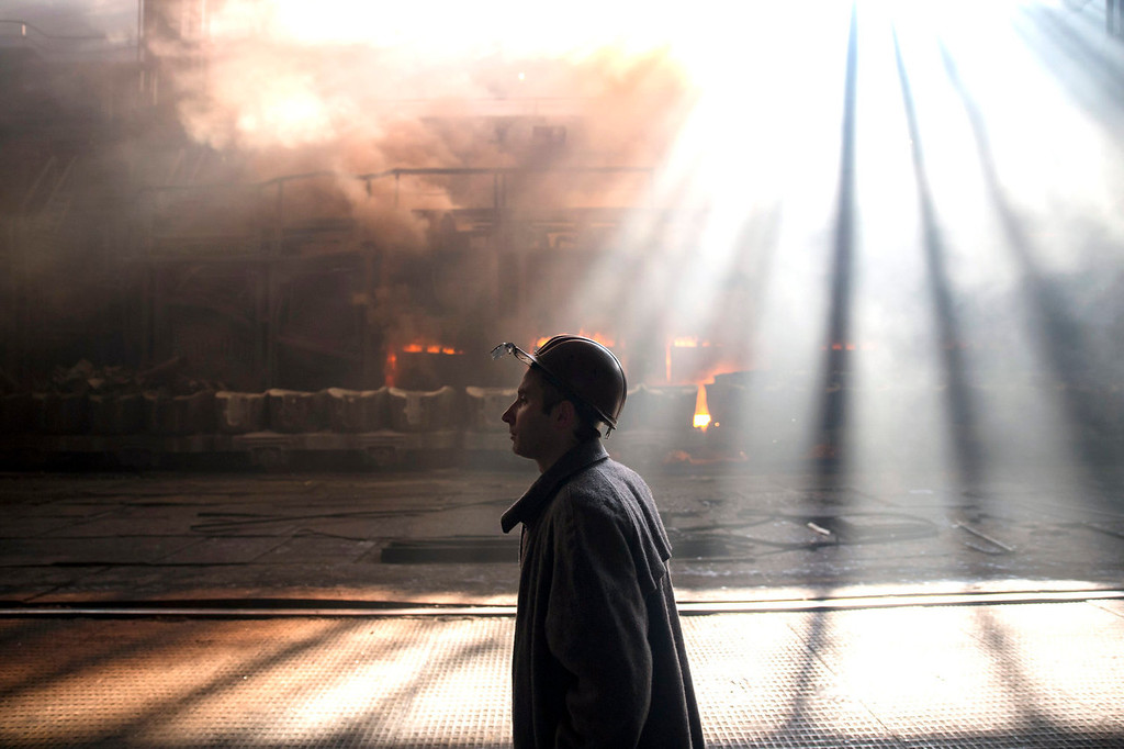 . An employee walks past the scrap metal furnace as sunlight streams through the windows at the Zaporizhstal steel plant, owned and operated by Metinvest BV, at their site in Zaporizhzhya, Ukraine, on Monday, Oct. 14, 2013. Metinvest BV, Ukraine\'s largest steelmaker, last year acquired 49.9% in steelmaker Zaporizhstal a manufacturer of semi-finished steel products, including hot and cold-rolled plates and coils. Photographer: Vincent Mundy/Bloomberg