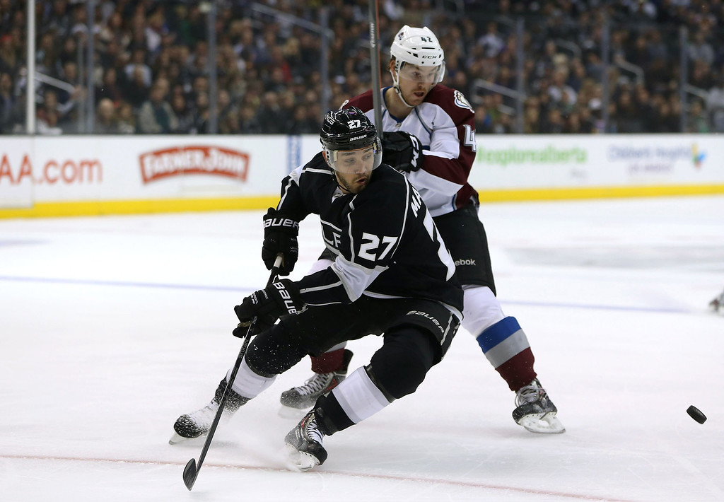 . LOS ANGELES, CA - NOVEMBER 23:  Alec Martinez #27 of the Los Angeles Kings skates after the puck while under pressure from Brad Malone #42 of the Colorado Avalanche during the NHL game at Staples Center on November 23, 2013 in Los Angeles, California.  (Photo by Victor Decolongon/Getty Images)