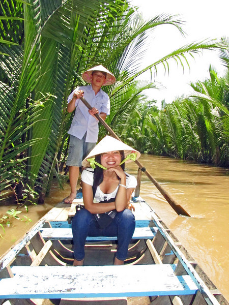 45-Teenage oarsman and guide, on rowboat in a Mekong side channel