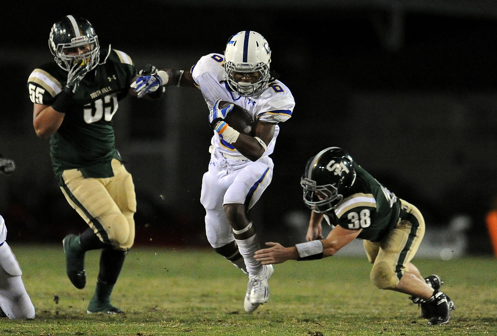 . Charter Oak\'s Zion Echols (6) runs through the defense of South Hills\' Ryan Rodriguez (55) and Mason Behr (38) in the first half of a prep football game at Covina DIstrict Field in Covina, Calif., on Thursday, Oct. 24, 2013. 