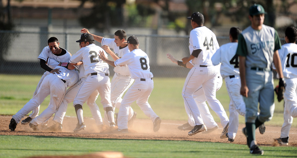 . Northview\'s Kollby Oriti is mobbed by teammates after walking with the bases loaded as teammate Alex Labor (not pictured) scores the winning run in the bottom of the seventh inning to defeat South (Torrance) 5-4 during a CIF-SS prep second round playoff baseball game against South (Torrance) at Northview High School on Tuesday, May 21, 2013 in Covina, Calif. 