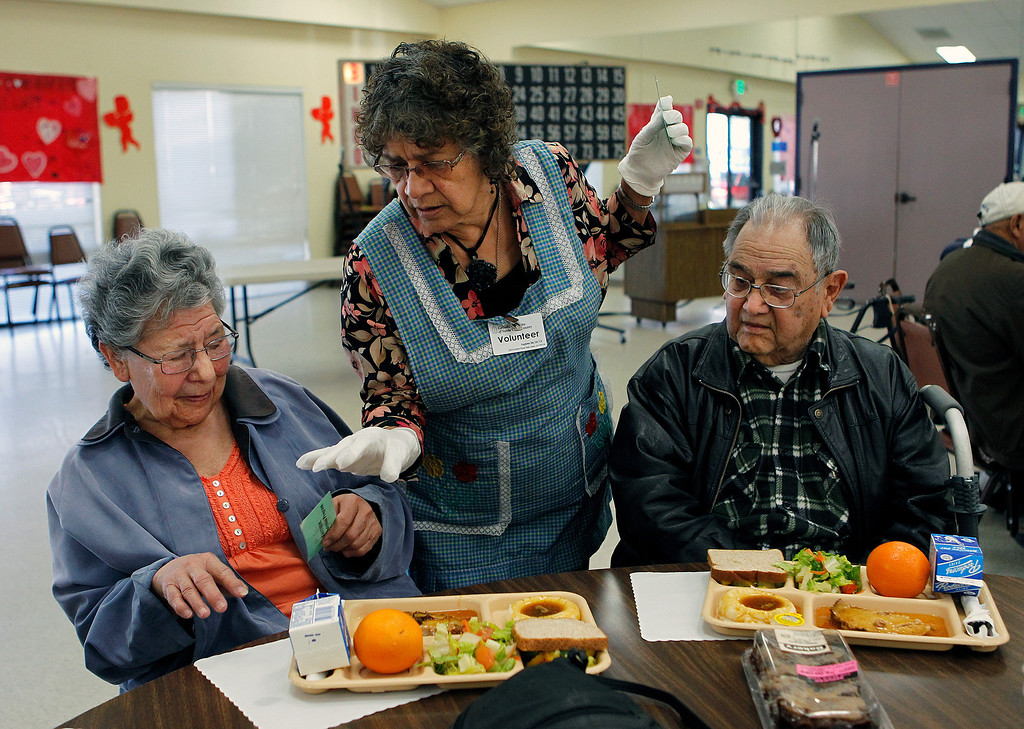 . At center, volunteer Rita Mora, serves Rebeca Murillo, left, and Josias Robledo, right, during a county subsidized lunch at the Eastside Neighborhood Center of the Catholic Charities of Santa Clara County in San Jose, Calif. on Wednesday, Feb. 27, 2013. (LiPo Ching/Staff)