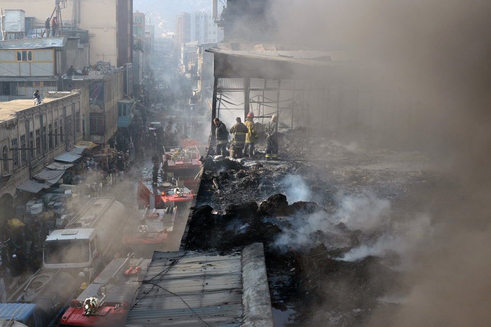 Description of . Afghan firefighters are pictured at the scene after a huge fire swept through a market in Kabul on  December 23, 2012.  A huge fire swept through a market in downtown Kabul on December 23, destroying hundreds of shops and forcing the city's nearby money exchange to evacuate, police and witnesses said. There were no reports of any casualties in the early morning blaze which destroyed most of the cloth market's 500 shops, Kabul fire department officials told AFP. SHAH MARAI/AFP/Getty Images