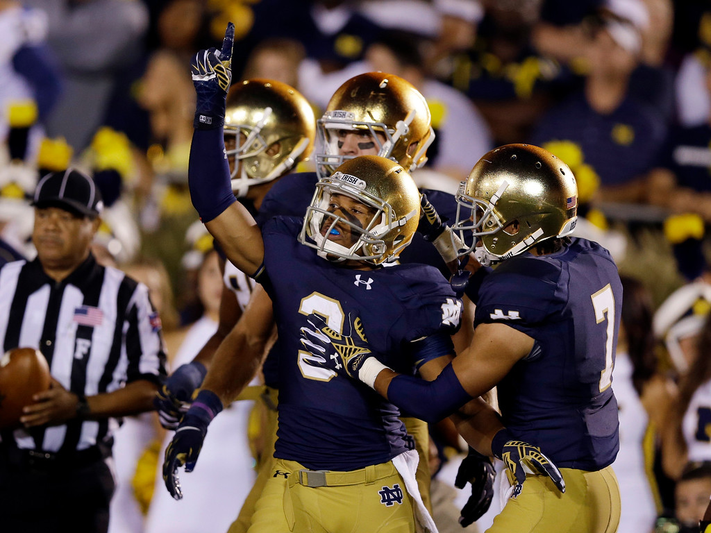 . Notre Dame wide receiver Amir Carlisle, center, celebrates a touchdown against Michigan during the first half of an NCAA college football game in South Bend, Ind., Saturday, Sept. 6, 2014. (AP Photo/Michael Conroy)