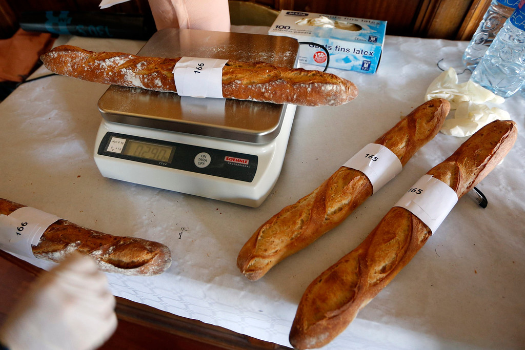 . An assistant weighs baguettes, French bread, registered in the competition for the \'Grand Prix de la Baguette de la Ville de Paris\' (Best Baguette of Paris 2013) annual prize at the Chambre Professionnelle des Artisans Boulangers Patissiers in Paris April 25, 2013. The baguette is a French cultural symbol par excellence and the competition saw 203 Parisian bakers who compete for recognition as finest purveyor of one of France\'s most iconic staples. The baguettes are registered, given anonymous white wrappings and an identification number. They are then carefully weighed and measured to ensure they do not violate the contest\'s strict rules. 52 entries were withdrawn for failing to measure between 55-70cm long or not matching the acceptable weight of between 250-300g. Every year, the winner earns the privilege of baking bread for the French President.   REUTERS/Charles Platiau