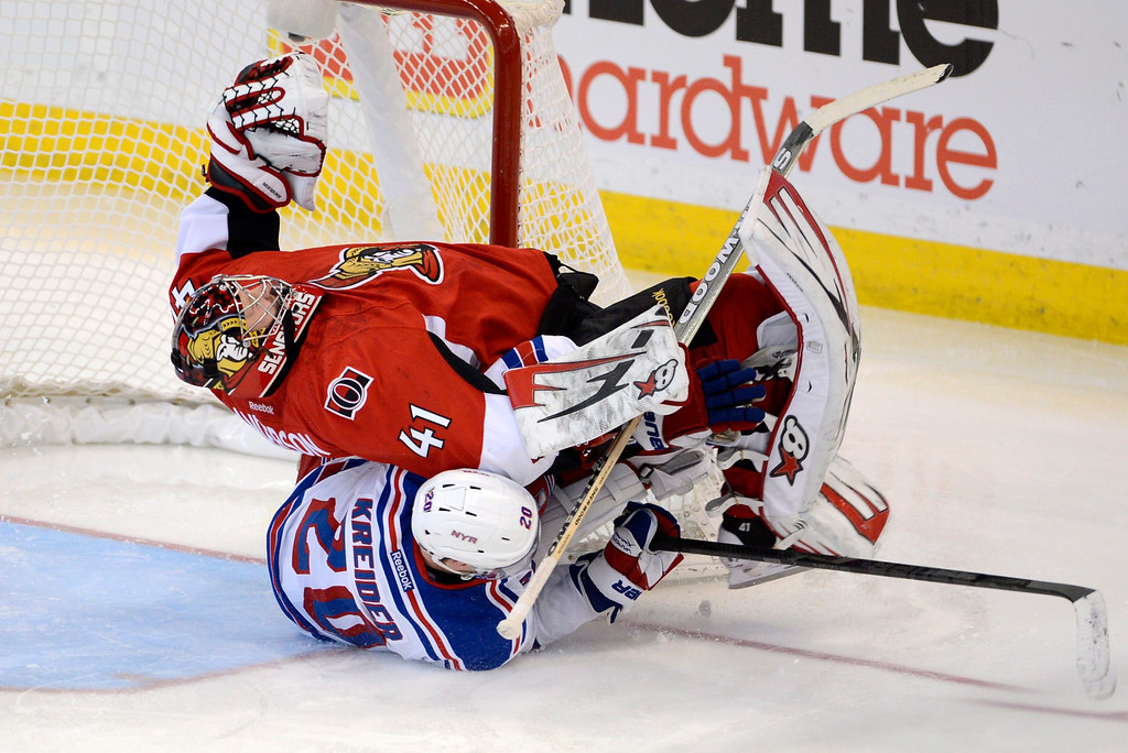 . Ottawa Senators goalie Craig Anderson is taken down New York Rangers\' Chris Kreider during the third period of an NHL hockey game in Ottawa, Ontario, Thursday, Feb. 21, 2013. (AP Photo/The Canadian Press, Adrian Wyld)