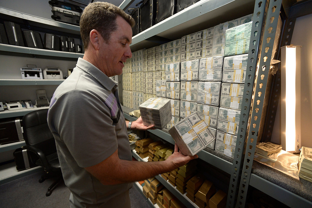 . Gregg Bilson, Jr. looks at some of the millions of dollars in fake money used for production. Bilson is the CEO of ISS Independent Studio Services, a prop house that holds hundreds of thousands of items used for motion pictures and television production. Runaway production has an impact on his business. Sunland, CA 12-31-2013. photo by (John McCoy/Los Angeles Daily News)