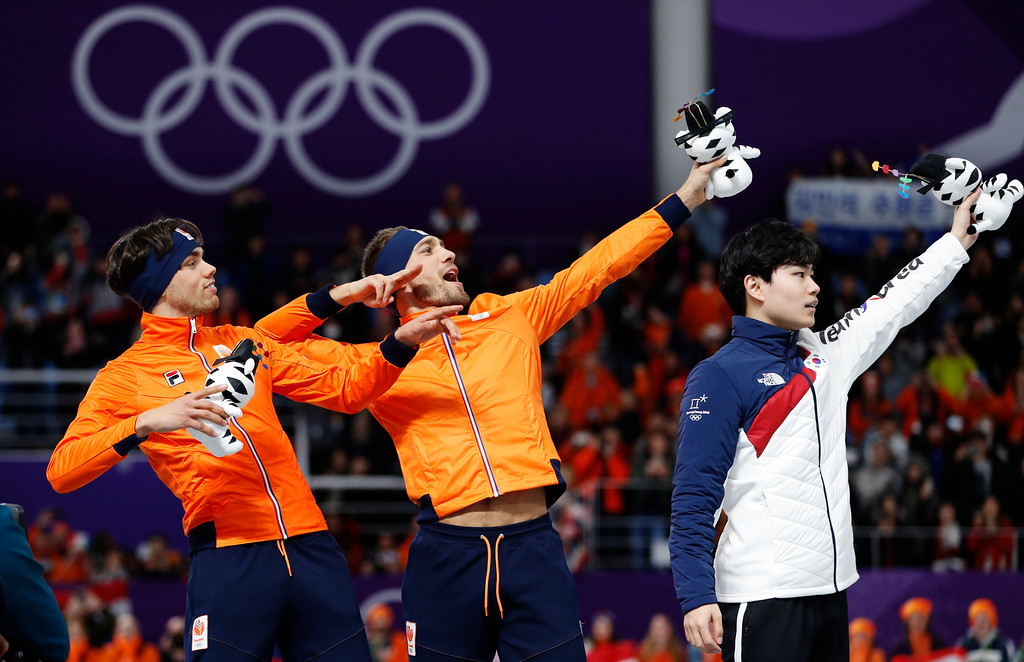 . Gold medallist Kjeld Nuis of The Netherlands, center, and silver medallist Patrick Roest of The Netherlands, left, imitate Jamaican sprinter Usain Bolt, on the podium with bronze medallist Kim Min-seok of South Korea, right, after the men\'s 1,500 meters speedskating race at the Gangneung Oval at the 2018 Winter Olympics in Gangneung, South Korea, Tuesday, Feb. 13, 2018. (AP Photo/John Locher)